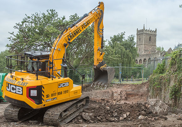 Digger starting work on site with Castle in back ground